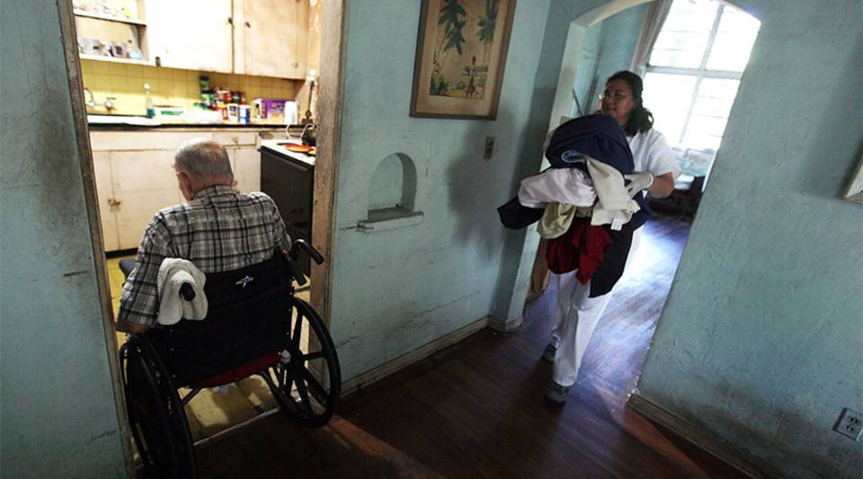 A home health aide helps an elderly man with his laundry in Miami.