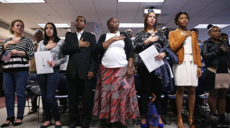 Immigrants stand for the national anthem before becoming American citizens at a naturalization ceremony held at the U.S. Citizenship and Immigration Services in New York City in 2013.