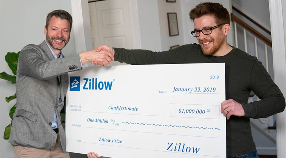 Stan Humphries, Zillow chief analytics officer, and Jordan Meyer, of Raleigh, North Carolina, celebrate Meyer's team's $1 million win of Zillow Prize, Zillow's competition to improve the accuracy of the Zestimate.