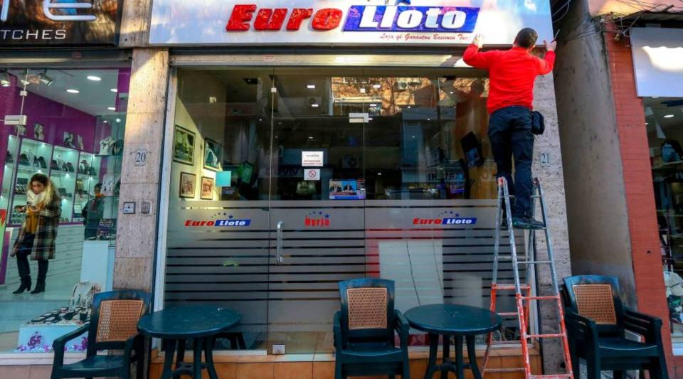 This picture taken on December 19, 2018, shows a man removing a sign from a betting establishment in downtown Tirana, Albania.