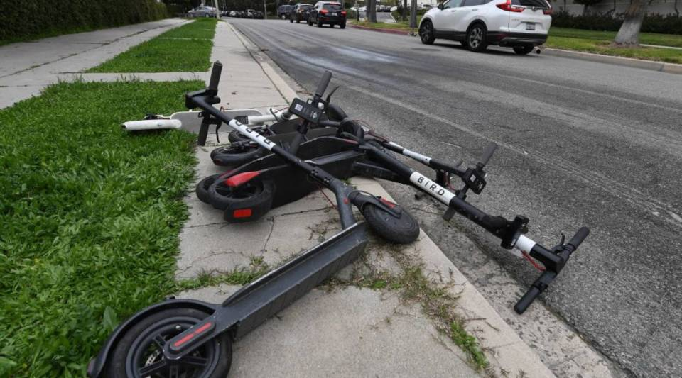 Shared electric scooters lie on a sidewalk in Los Angeles, California on February 13, 2019.