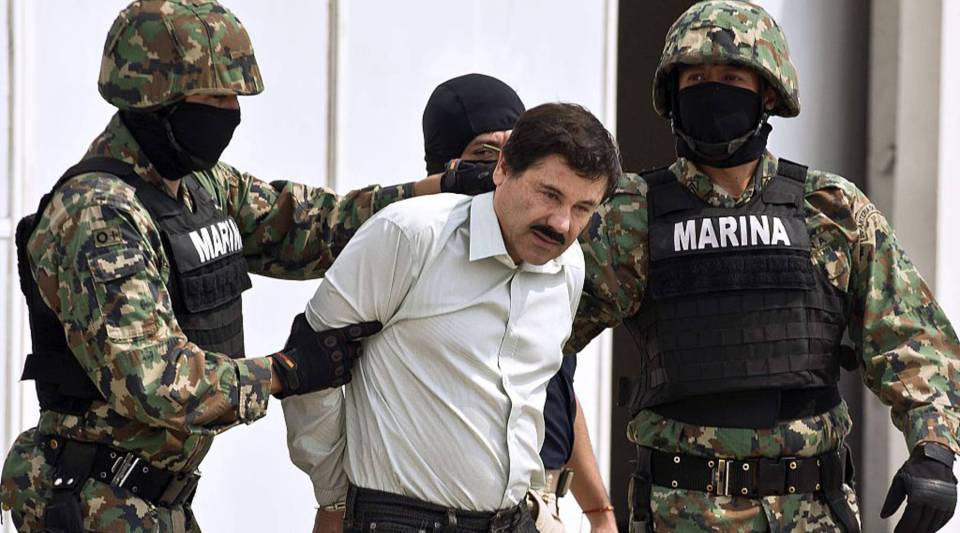 Mexican drug trafficker Joaquín Guzmán Loera, is escorted by marines as he is presented to the press on Feb. 22, 2014 in Mexico City.