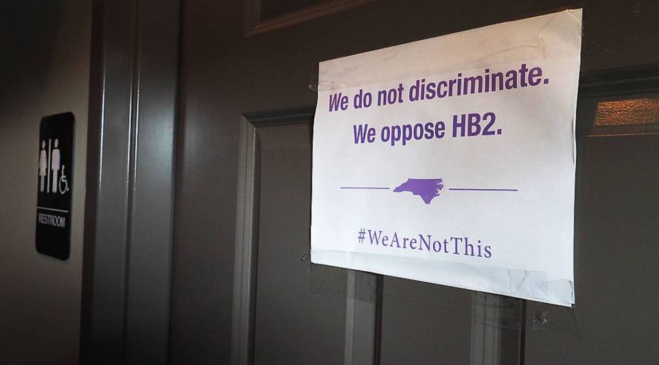 A unisex sign and the 'We Are Not This' slogan are outside a bathroom at Bull McCabes Irish Pub on May 10, 2016 in Durham, North Carolina.