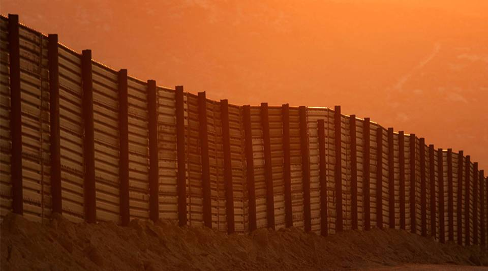 Dusk falls over a section of the U.S.-Mexico border fence near Campo, California.