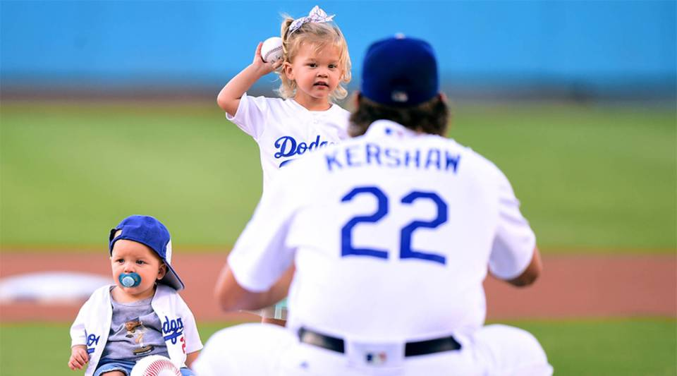 Cali Ann Kershaw throws out a ceremonial first pitch to her dad Clayton Kershaw #22 of the Los Angeles Dodgers as brother Charley Kershaw sits on the mound before the game against the Minnesota Twins at Dodger Stadium on July 26, 2017 in Los Angeles, California.