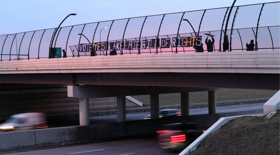 Members of a grassroots group called Toledoans for Safe Water set up a sign on a highway overpass urging people to vote for the Lake Erie Bill of Rights.