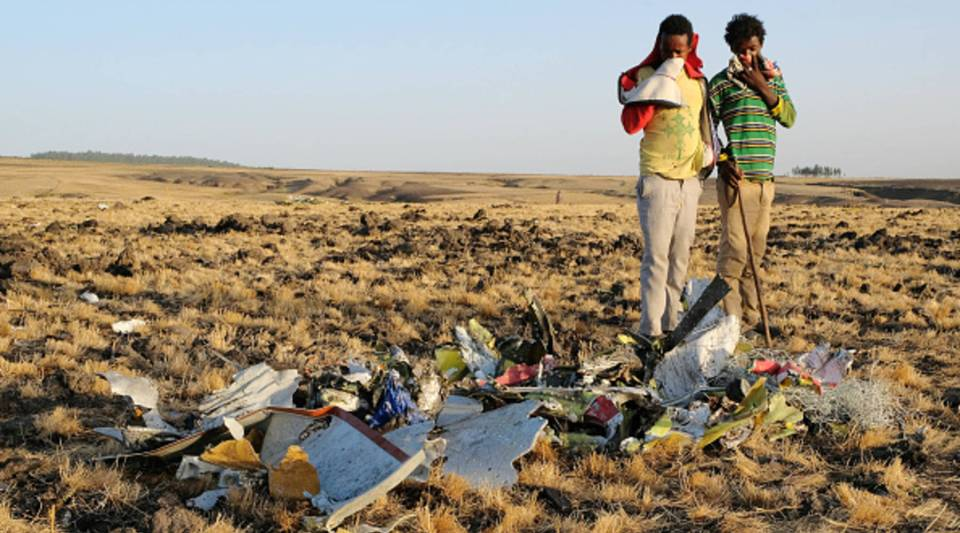 Two local boys examine a pile of twisted metal gathered by workers during the continuing recovery efforts at the crash site of Ethiopian Airlines flight ET302 on March 11, 2019 in Bishoftu, Ethiopia.