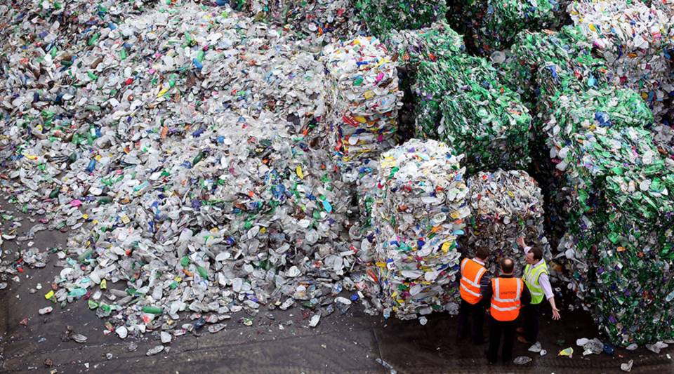 An employee walks people through the recycling process at a closed loop plant in London, United Kingdom in 2010.