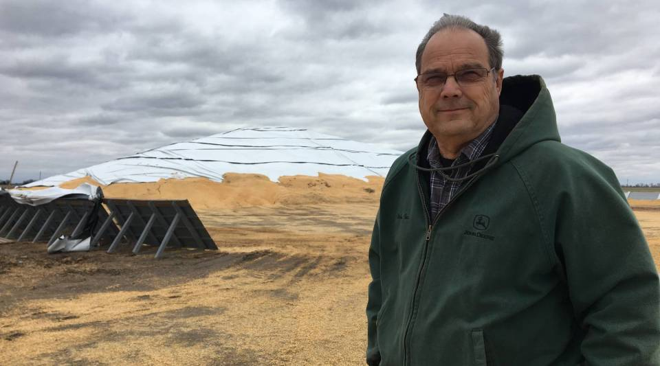 Farmer Tom Giessel stands in front of a corn pile near Larned, Kansas. The corn was grown in 2017 and because of a market glut, it still hasn't sold.