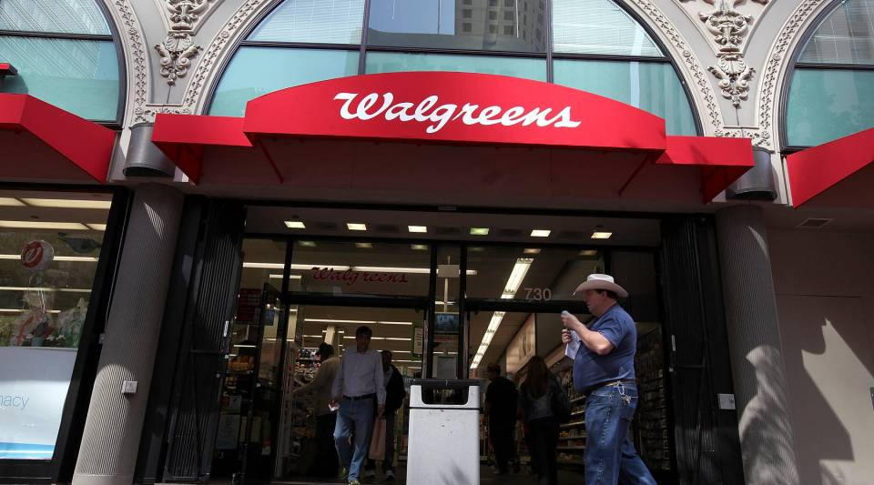 People walk by a Walgreens store in San Francisco. The pharmacy industry thinks bigger is better to find cost savings.