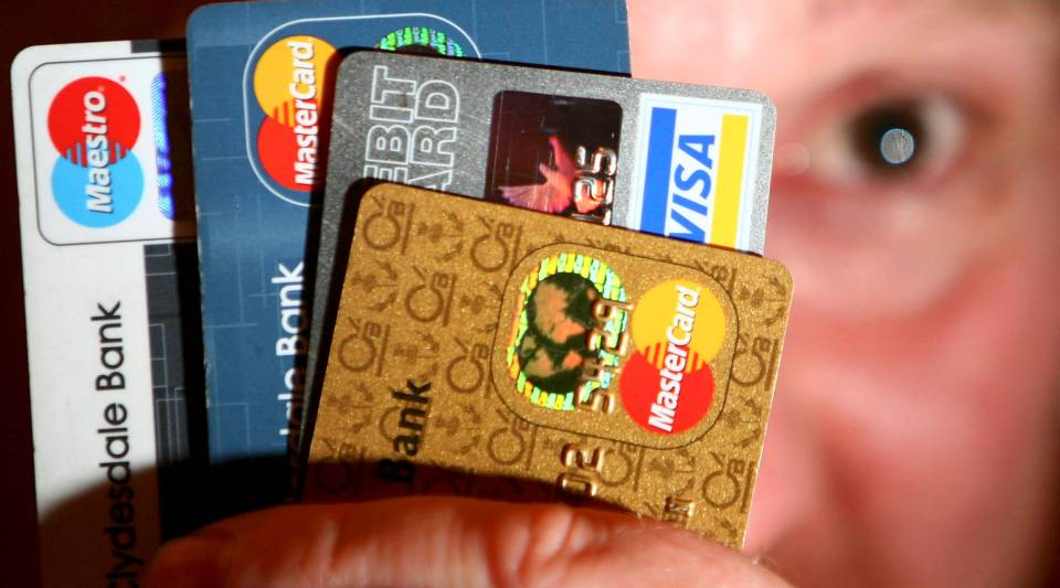 A man holds up some credit and debit cards