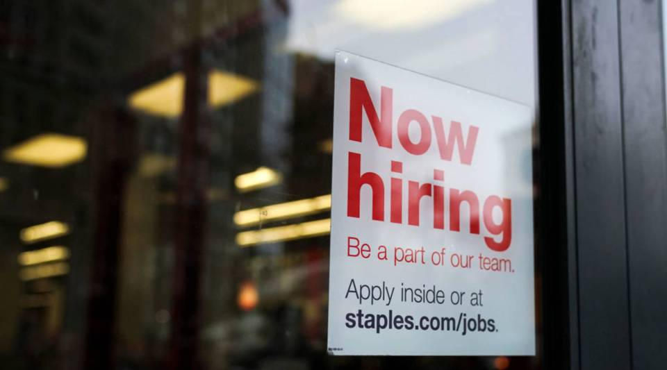 A 'now hiring' sign hangs on the door of a Staples store in Lower Manhattan, January 4, 2019 in New York City.