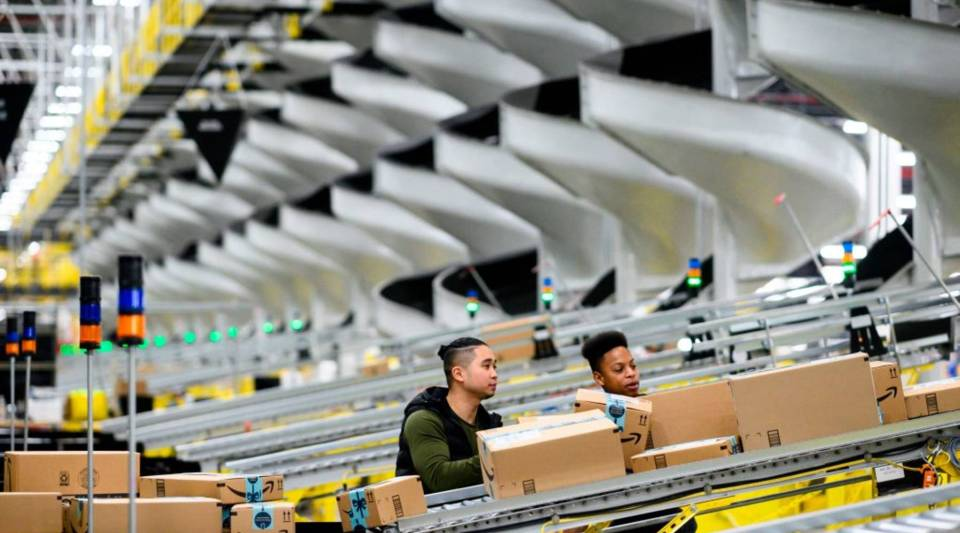 Men work at a distribution station in the 855,000-square-foot Amazon fulfillment center in Staten Island, New York, in February.