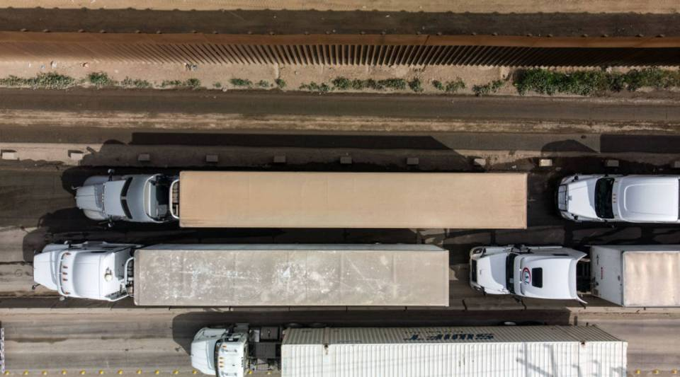 Aerial view of cargo trucks lining up to cross to the United States near the US-Mexico border at Otay Mesa crossing port in Tijuana, Baja California state, Mexico, on April 4, 2019. US President Donald Trump is expected to visit a section of the border fence in Calexico during his tour to California on Friday.