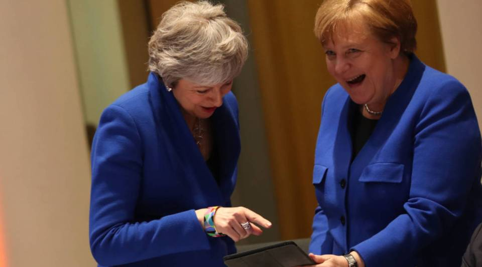 British Prime Minister Theresa May, left, and German Chancellor Angela Merkel look at a tablet ahead of a European Council meeting on Brexit at the Europa Building at the European Parliament in Brussels on April 10.