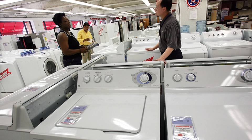 Customers look at Maytag and Whirlpool washers and dryers in New York City.