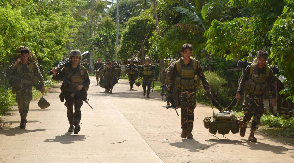 Philippine soldiers walk along a highway as they return to camp after an armed encouter with members of militant kidnap-for-ransom group, Abu Sayyaf, in the Sulu province on the southern island of Mindanao on August 26, 2016.