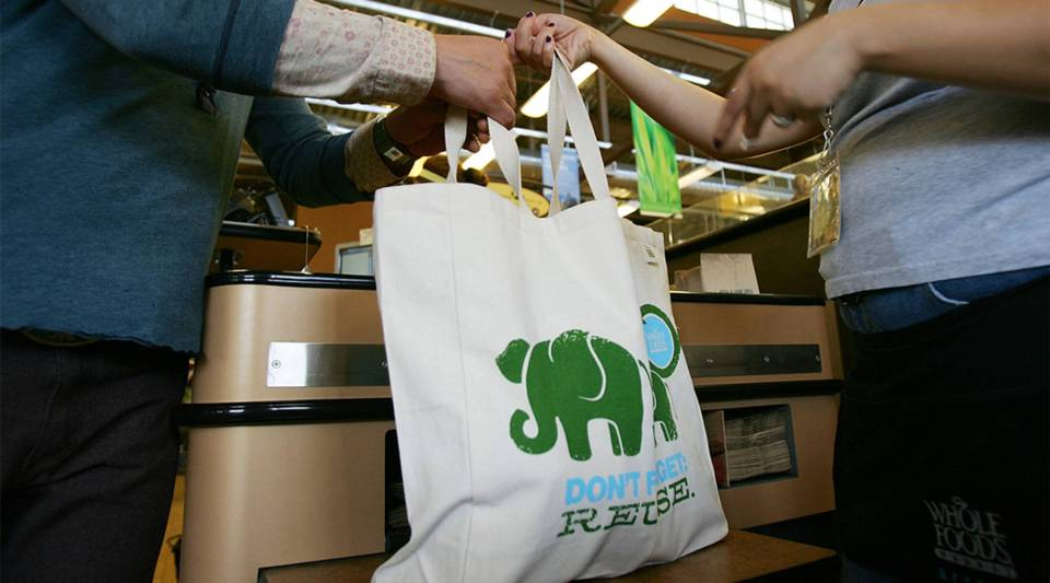Employees hand out free reusable grocery bags at a Whole Foods Market in 2008 in Pasadena, California.