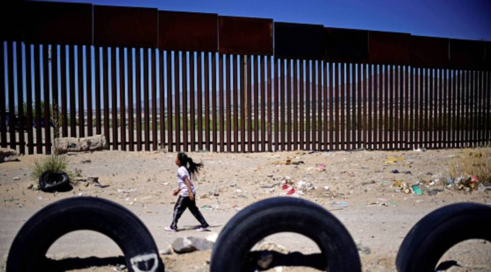 A Mexican girl walks near by the metal fence between Ciudad Juarez, Cihuahua state, Mexico and Sunland Park, New Mexico, U.S., on May 3, 2018.