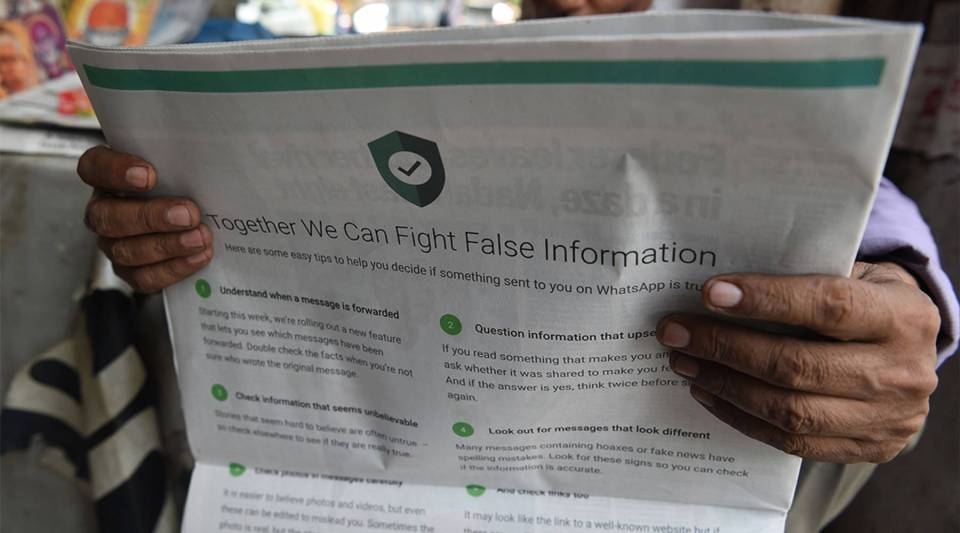 An Indian newspaper vendor reads a newspaper with a full back page advertisement from WhatsApp intended to counter fake information in New Delhi on July 10, 2018.