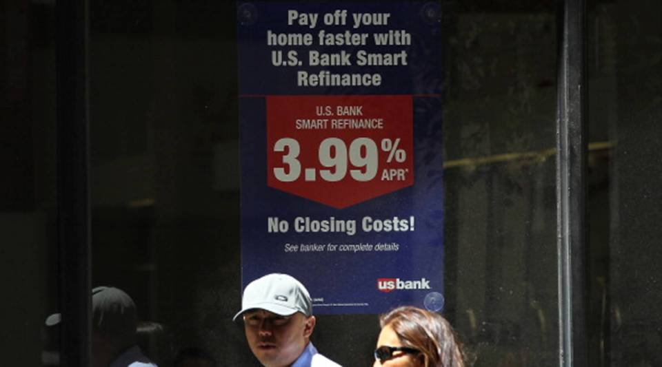 Pedestrians pass by a sign advertising low refinance rates at a US Bank office in San Francisco, Calif.