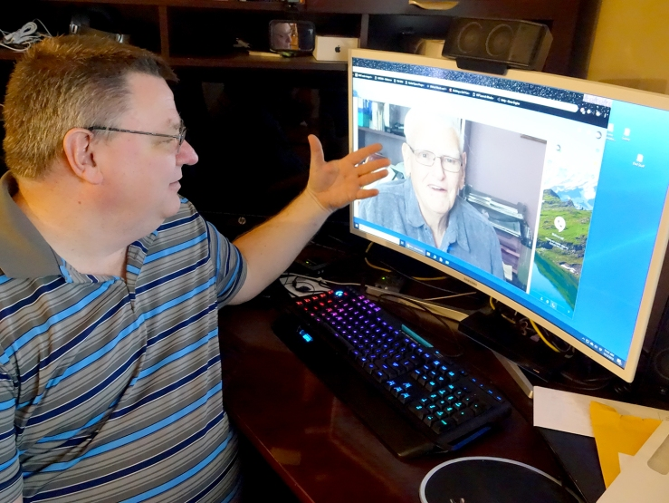 Chad Schreiber, who lives in a St. Louis, Missouri suburb, gestures toward a photo of his father, Art, on his computer.
