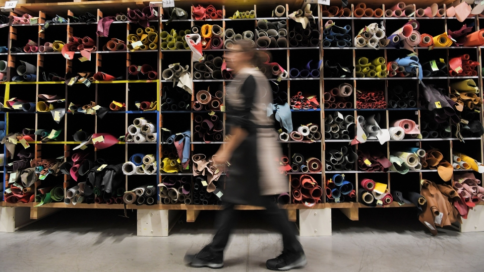 A craftwoman passes by pieces of leather on October 12, 2018 at the Louis Vuitton leather work factory in Juilley, western France. Fashion giant LVMH Moët Hennessy Louis Vuitton has signed a five-year biodiversity partnership with UNESCO, committing to an ambitious set of environmental goals.
