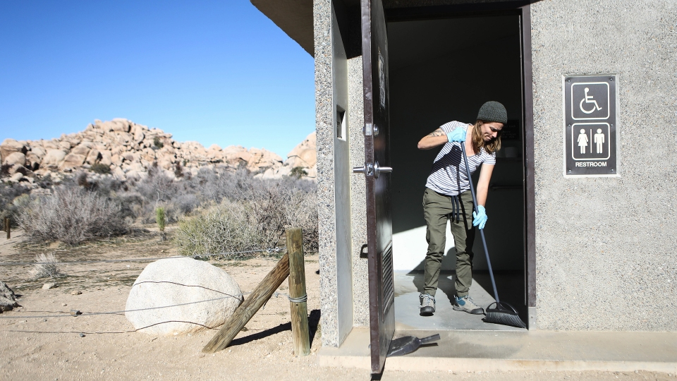 A volunteer cleans a restroom at Joshua Tree National Park on January 4, 2019 in California.