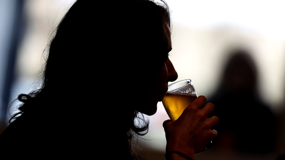 A customer sips on a glass of craft beer at a California brewery.