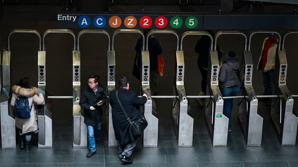 Customers move through the turnstiles at the Fulton Center subway station on February 27, 2019 in New York City.