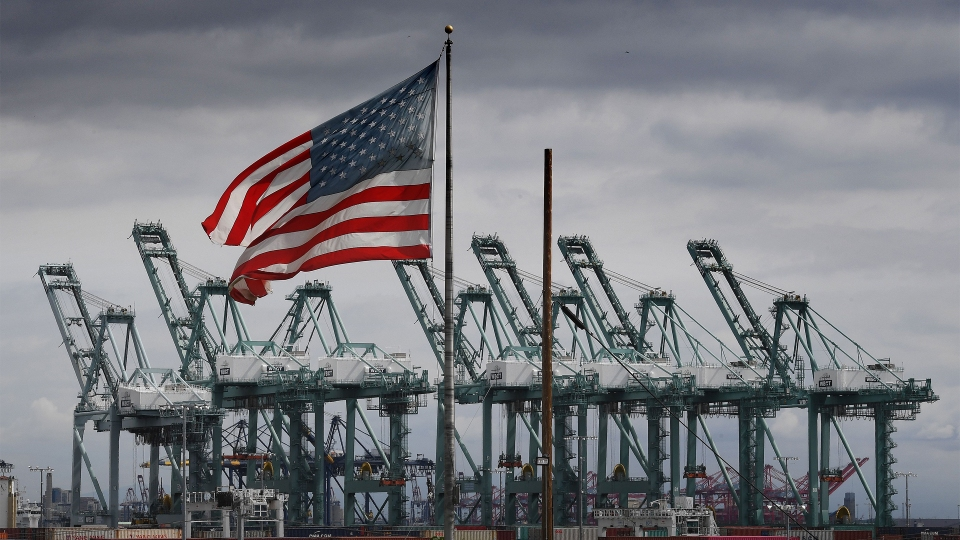 The U.S. flag flies over shipping cranes and containers in Long Beach, California, in March.