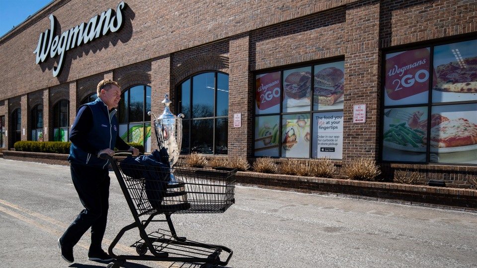 Senior PGA champion Paul Broadhurst pushes a shopping cart carrying his trophy outside of a Wegmans grocery store during a media tour on March 26, 2019 in Rochester, New York.
