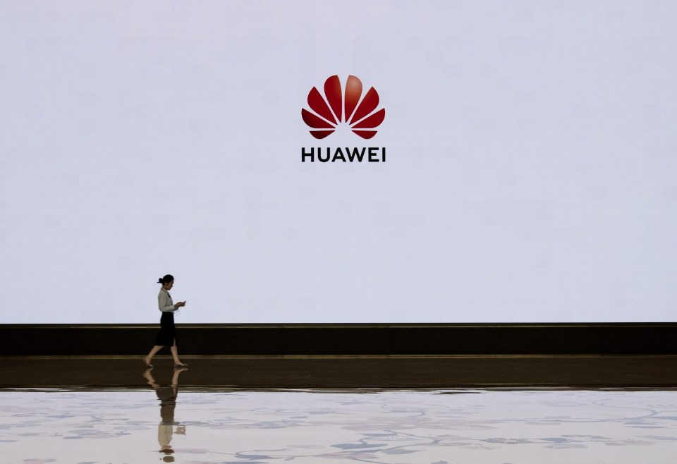 SHENZHEN, CHINA - APRIL 12: A member of Huawei's reception staff walks in front of a large screen displaying the logo in the foyer of a building used for high profile customer visits and displays at the company's Bantian campus on April 12, 2019 in Shenzhen, China.