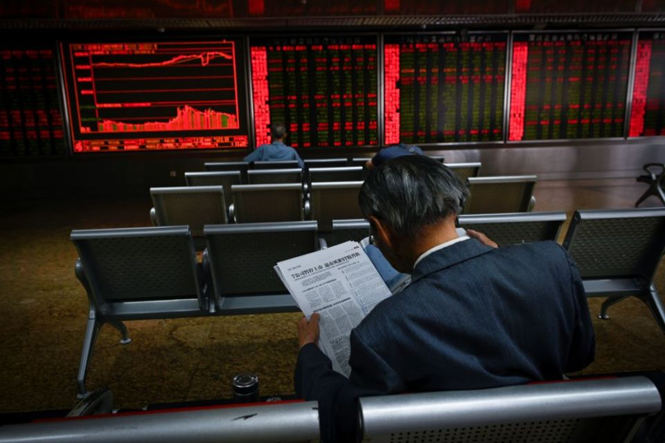 An investor reads a newspaper in front of screens showing stock market movements at a securities company in Beijing on May 14, 2019.