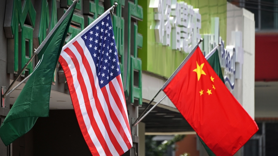 The U.S. and Chinese flags are displayed outside a hotel in Beijing.