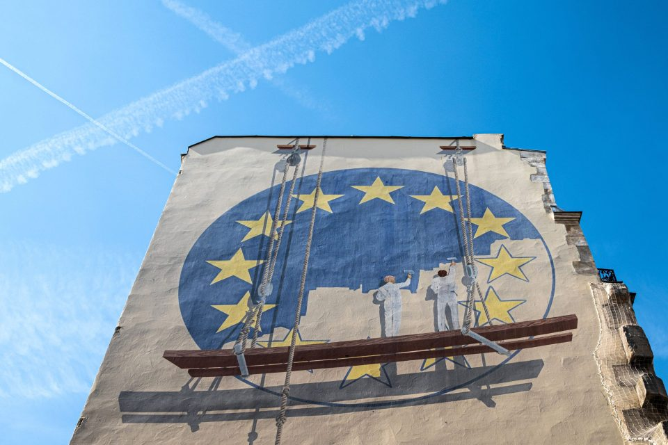 A trompe l'oeil shows two workers painting the European Union flag on the side of a building in the French capital Paris on May 23, 2019. - Europe kicked off voting across the continent in a contest in which rising populist forces are hoping to make significant gains, threatening closer EU integration.
