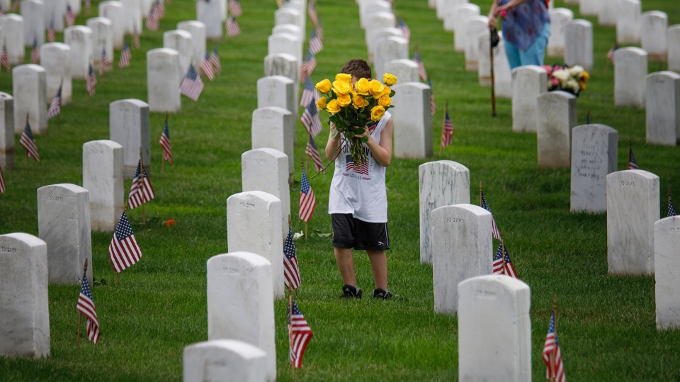 A volunteer places flowers along a row of headstones during a volunteer event ahead of Memorial Day on May 26, 2019 in Arlington, Virginia.