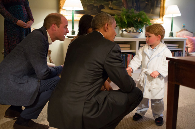 Former US President Barack Obama, Prince William, Duke of Cambridge and former First Lady Michelle Obama talk with Prince George at Kensington Palace on April 22, 2016 in London.
