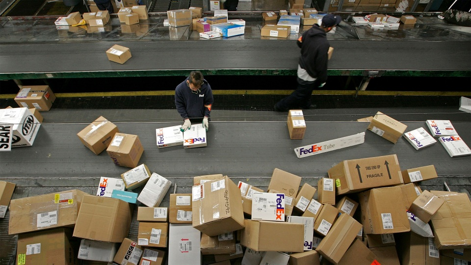 A FedEx worker sorts packages on a conveyor belt at the FedEx Oakland International Airport sort facility in California.