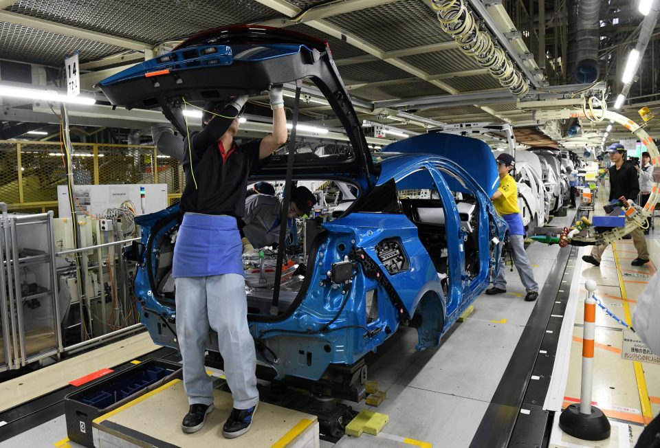 This December 8, 2017 picture shows workers assembling fourth generation Toyota Prius cars on the production line at the company's Tsutsumi assembly plant in Toyota City, Aichi prefecture.