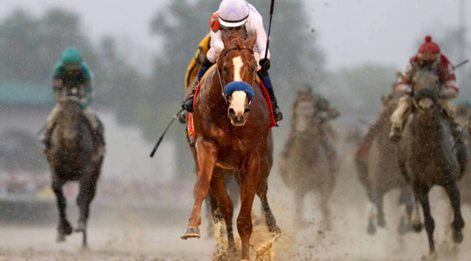 Justify, ridden by jockey Mike Smith, crosses the finish line to win the 144th running of the Kentucky Derby at Churchill Downs on May 5, 2018, in Louisville, Kentucky.