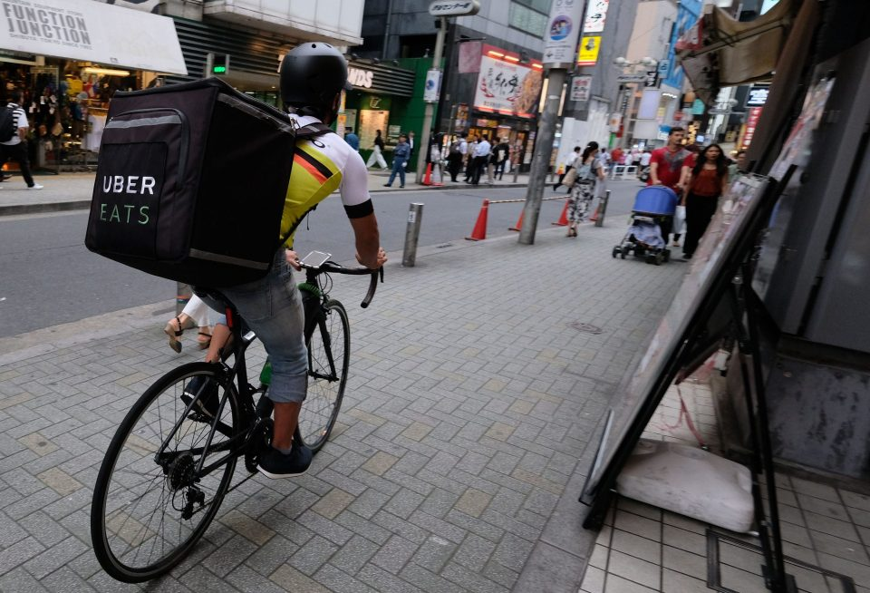 A man delivers a food order by bicycle for Uber Eats in Tokyo's Shibuya shopping district in 2018.