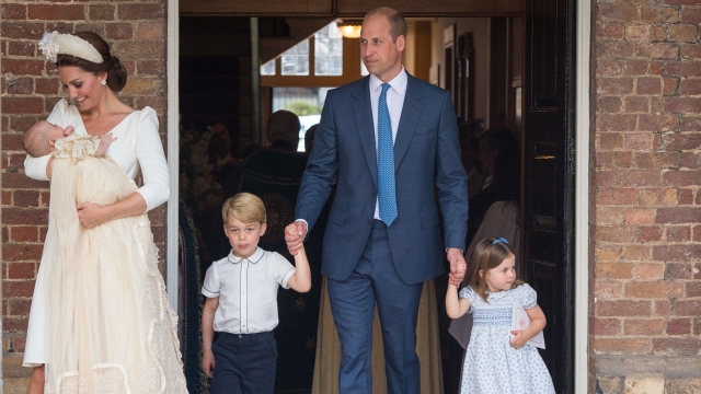 Britain's Princess Charlotte of Cambridge and Britain's Prince George of Cambridge hold hands with their father, Britain's Prince William, Duke of Cambridge, as Britain's Prince Louis of Cambridge is carried by his mother, Britain's Catherine, Duchess of Cambridge after his christening service at the Chapel Royal, St James's Palace, London on July 9, 2018.