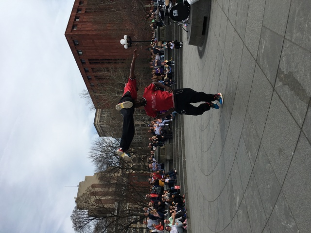 Kareem Barnes spins his brother Tyheem in front of a large crowd in Washington Square Park. The acrobatic dancing duo collect both cash and digital donations.