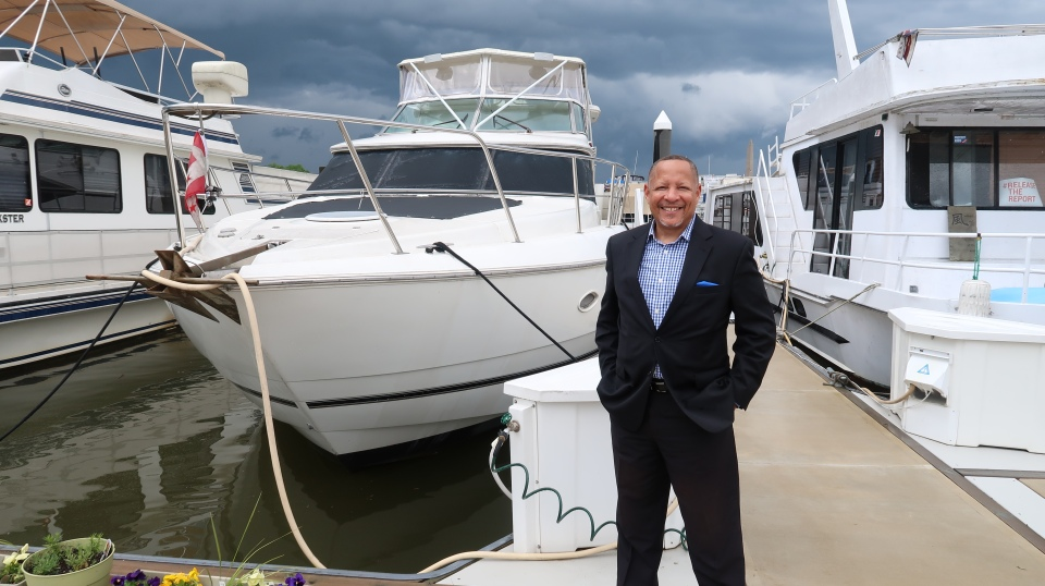 Darryl Madden, a full-time liveaboard boater, next to his 50-foot cruiser in Southwest D.C.