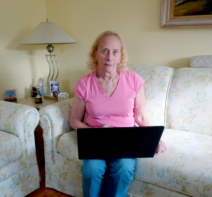 Judy, 79, sits with a laptop.