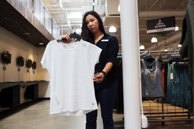 """Lili Luong, General Manager at Columbia Sportswear Company Employee Store, holding an example of a garment with a """"nurse's pocket"""" or """"chapstick pocket"""" which lowers the duty rate."""