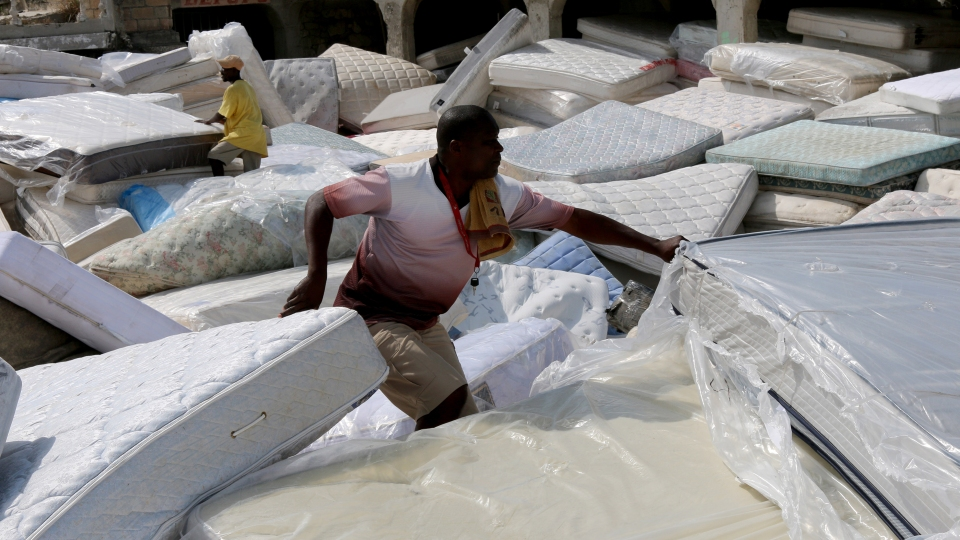 """Wilson Simon sorts through used mattresses for resale in Port-de-Paix, Haiti. A mattress is one of the most sought after commodities in the underground, break-bulk shipping industry between Miami and Haiti and is considered to be """"gold"""" among vendors."""