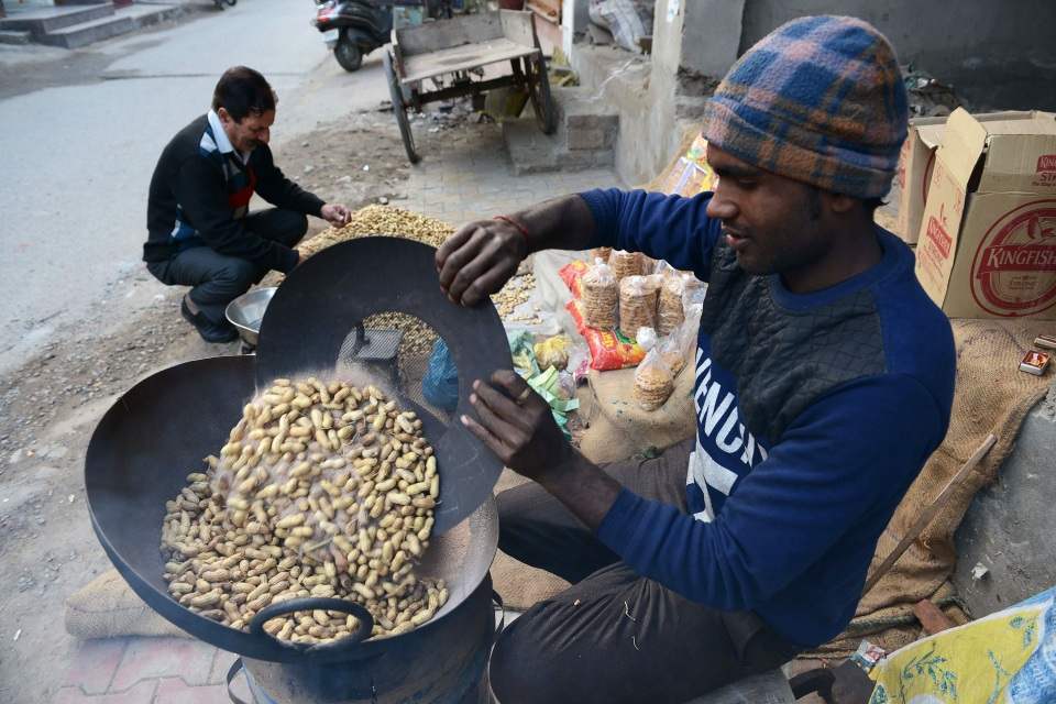 An Indian vendor roasts peanuts at a roadside stall in Amritsar in 2018.