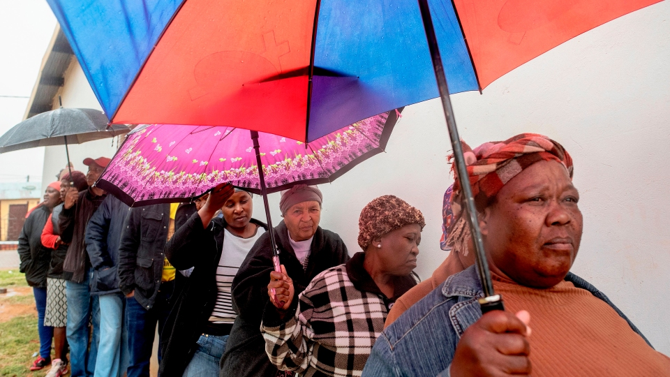 People queue to vote for South Africa's national and provincial elections at a polling station in the Tlhabologang township in Coligny on May 8, 2019. - South Africans voted on May 8 in the country's sixth democratic general election since the end of apartheid in 1994.